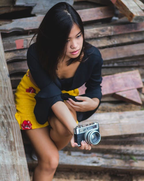 Woman Sitting on Stair While Holding Camera