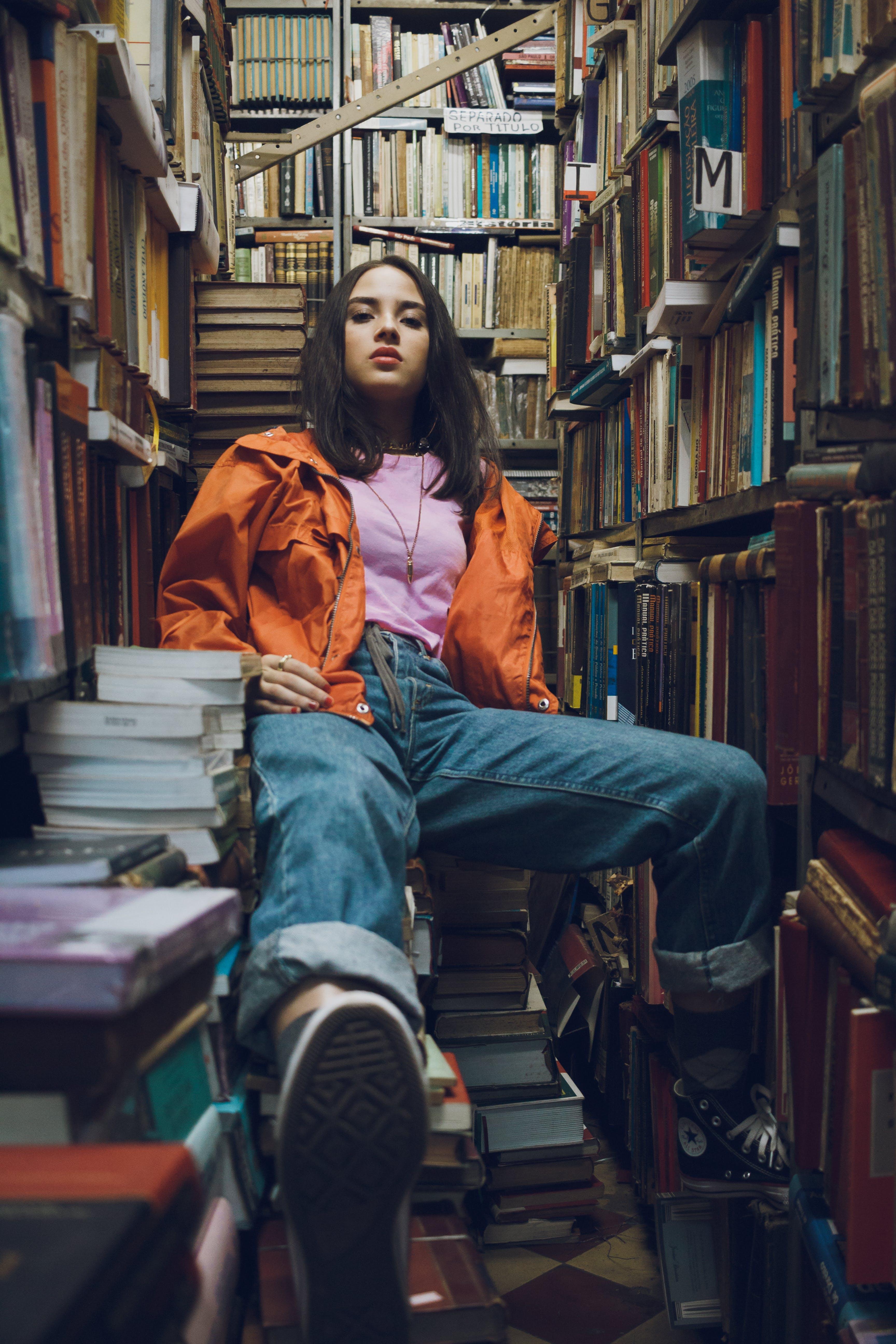 Woman Sitting Between Bookshelves