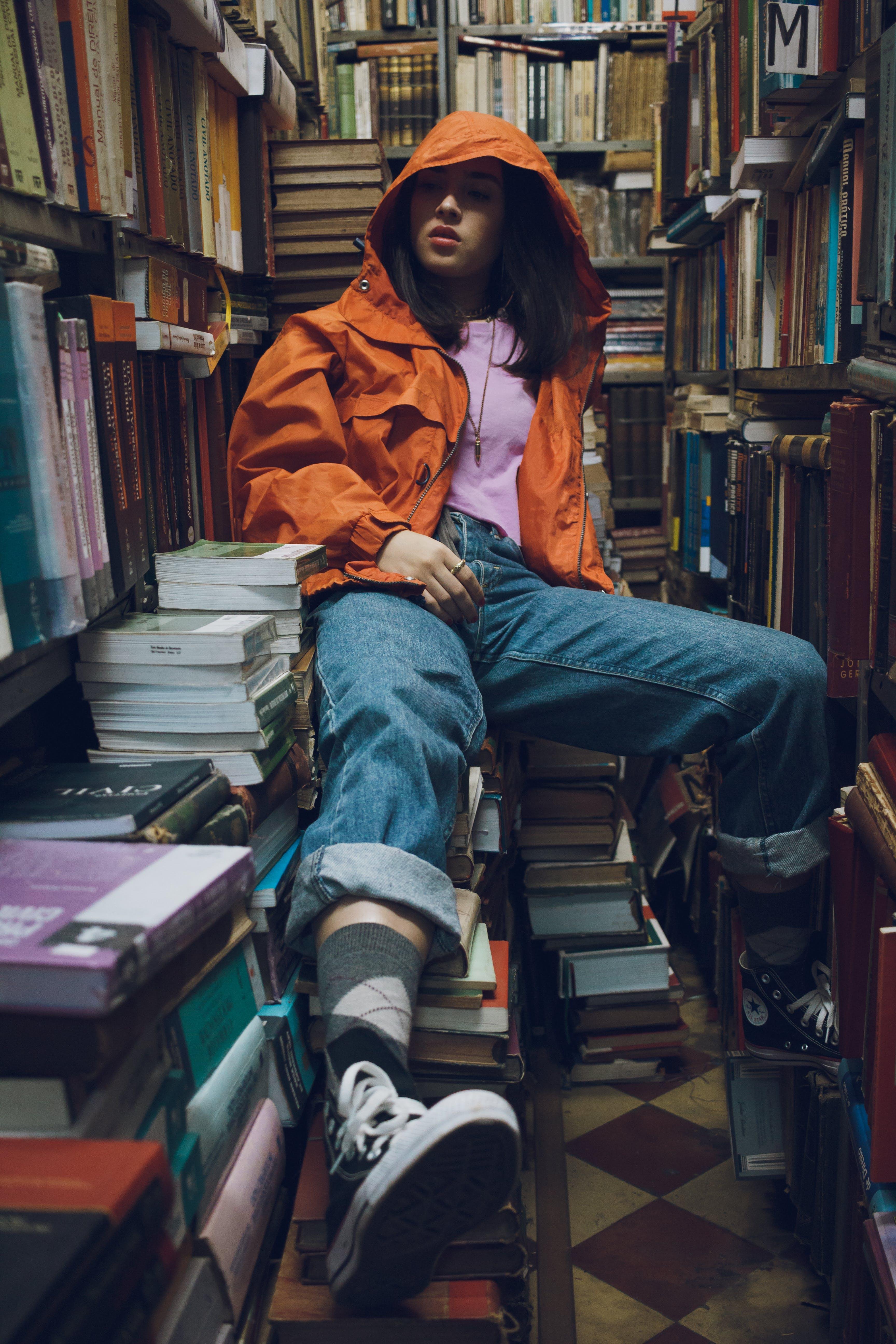 Woman Wearing Orange Jacket Sitting Inside Library
