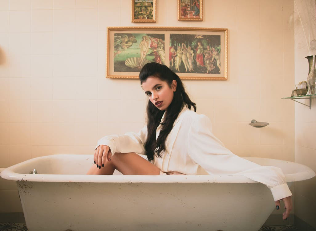 Woman in White Long-sleeved Shirt Sitting on White Ceramic Bathtub
