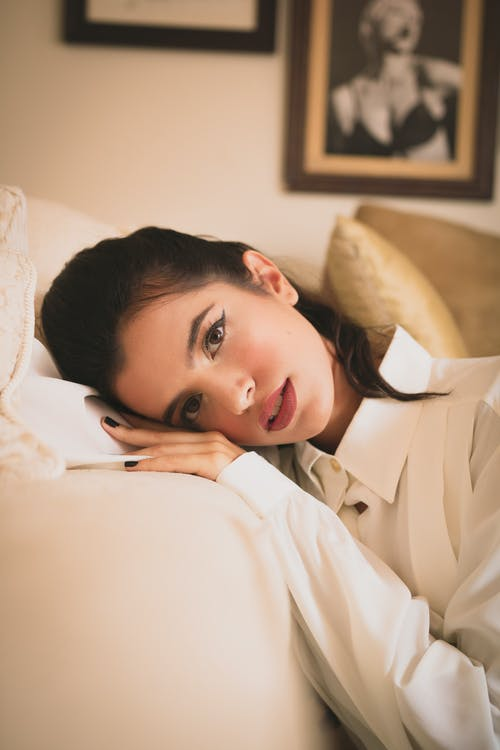 Woman Leaning on White Sofa Inside Room