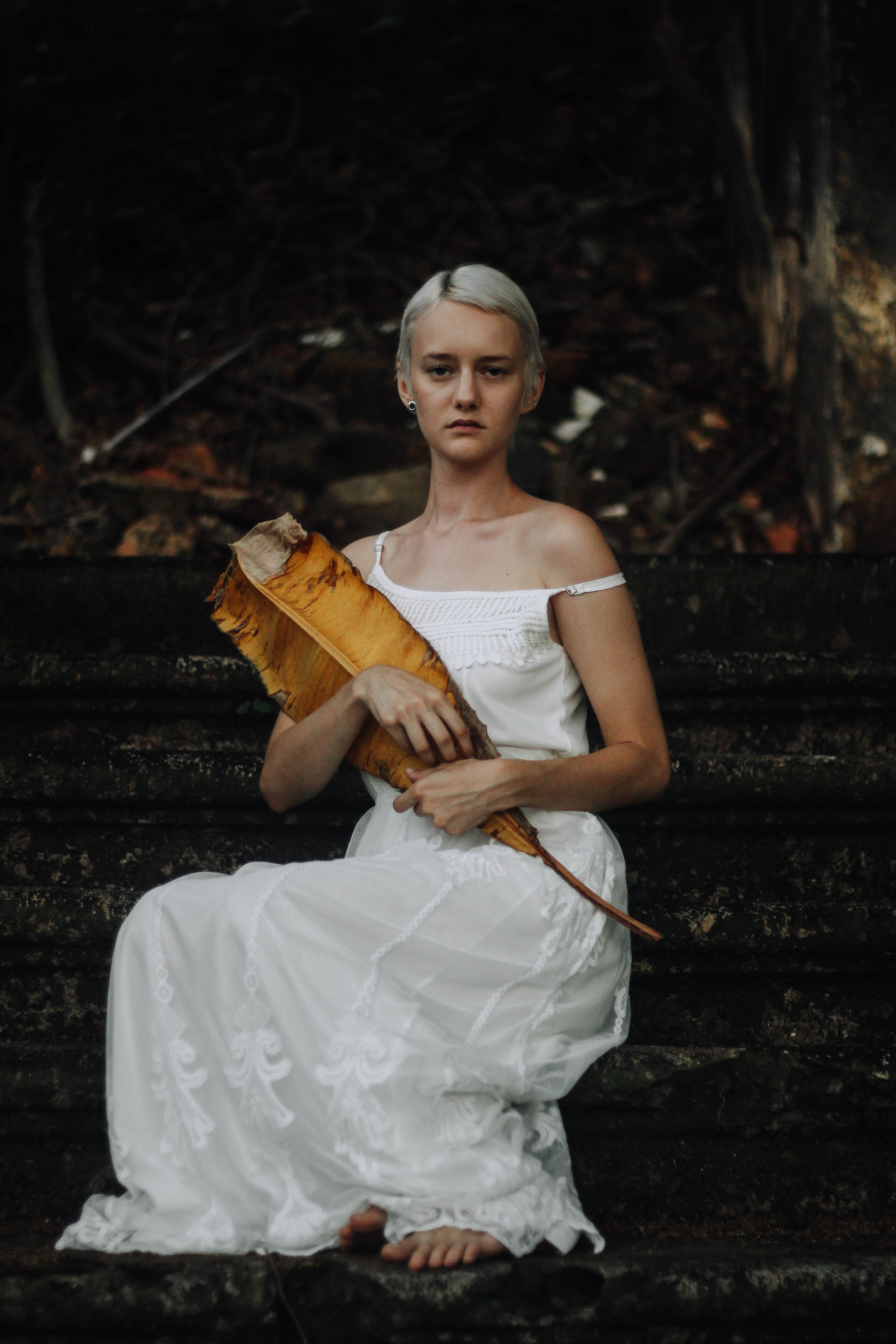 Photo of Woman in White Dress Sitting on Concrete Staircase Holding Dry Banana Leaf
