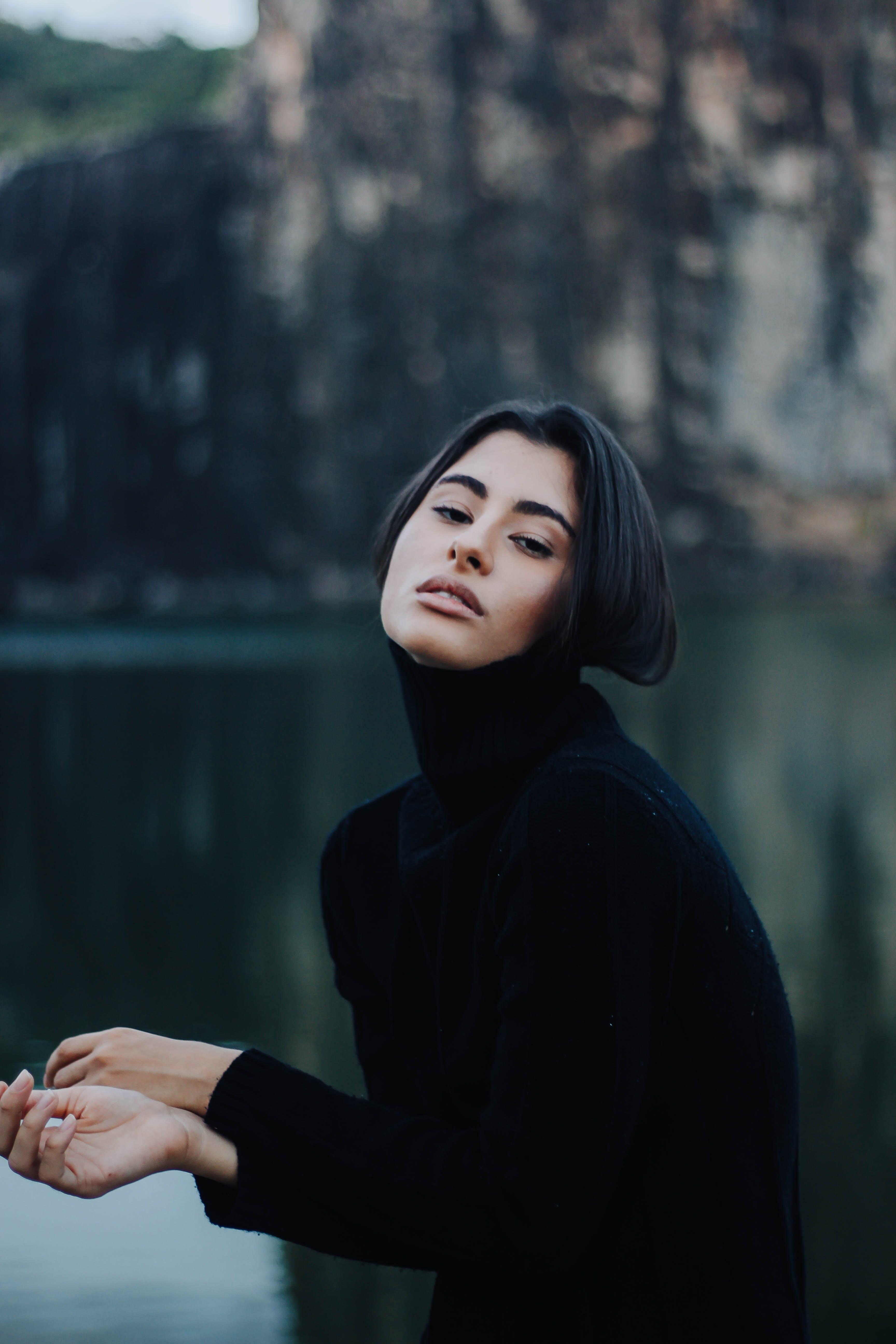 Woman in Black Turtleneck Sweater Standing Near Calm Body of Water