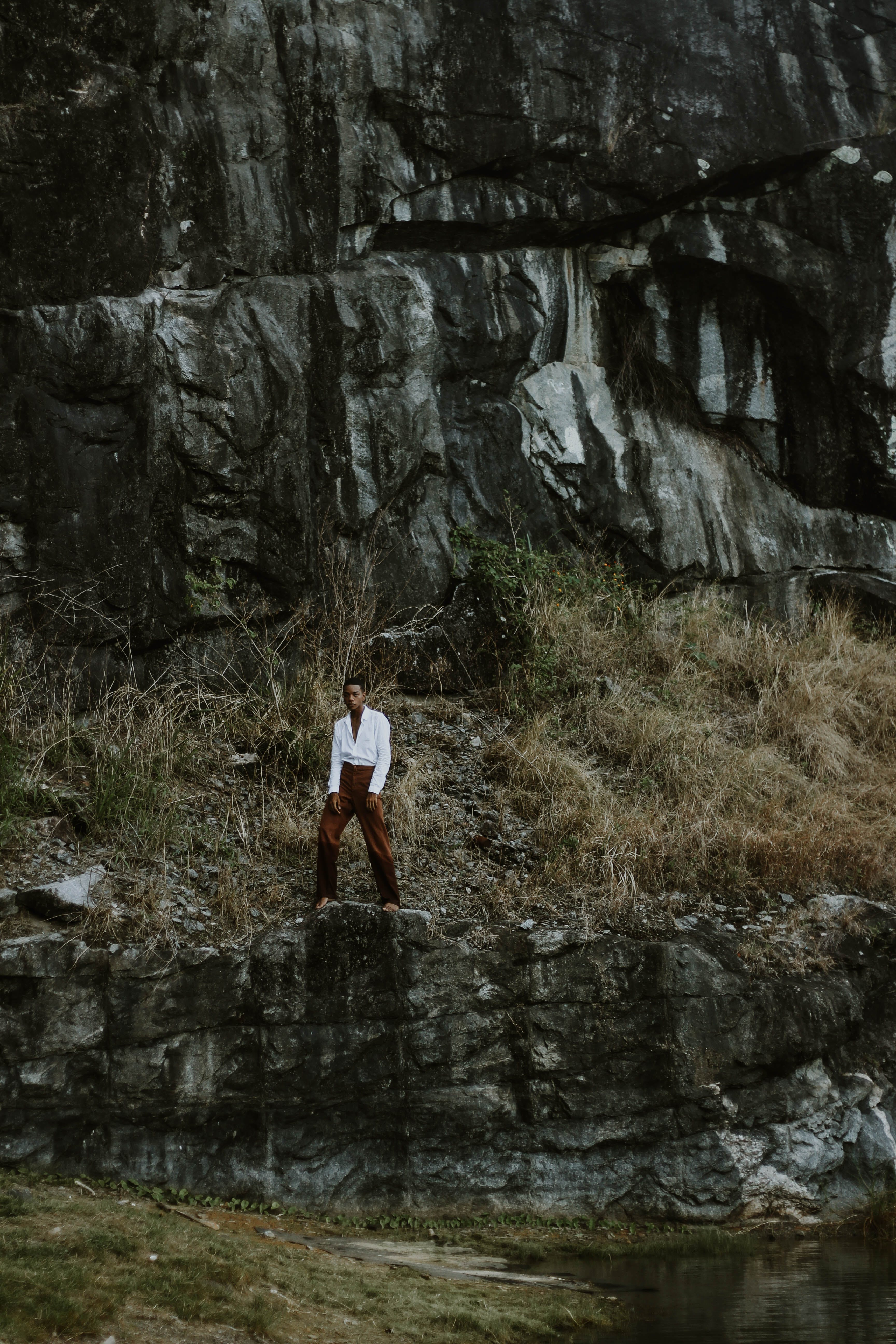 Man in White Long-sleeved Shirt and Maroon Pants Standing Near Cliff