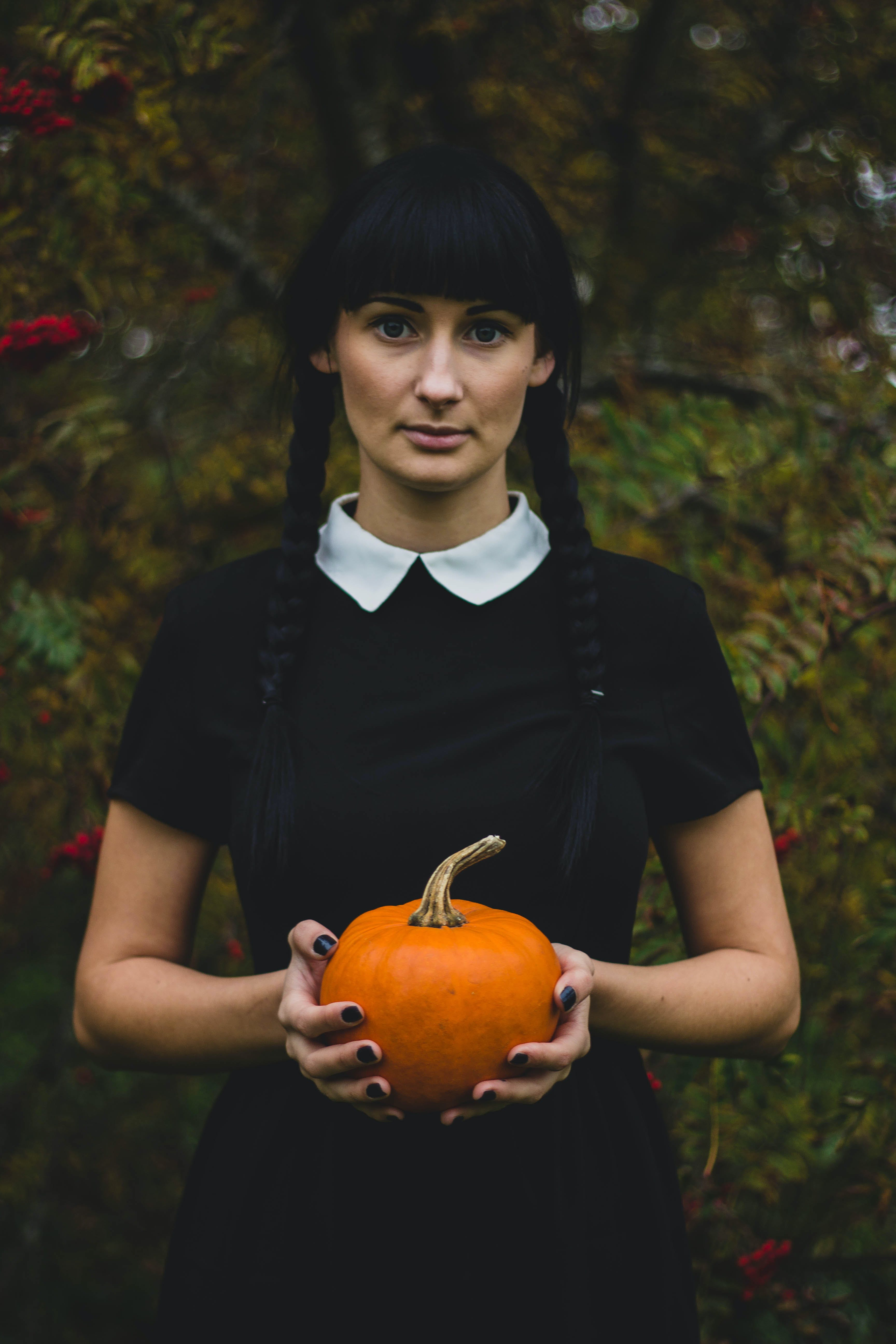 Woman in Black and White Collared Dress Holding Pumpkin during Daytime