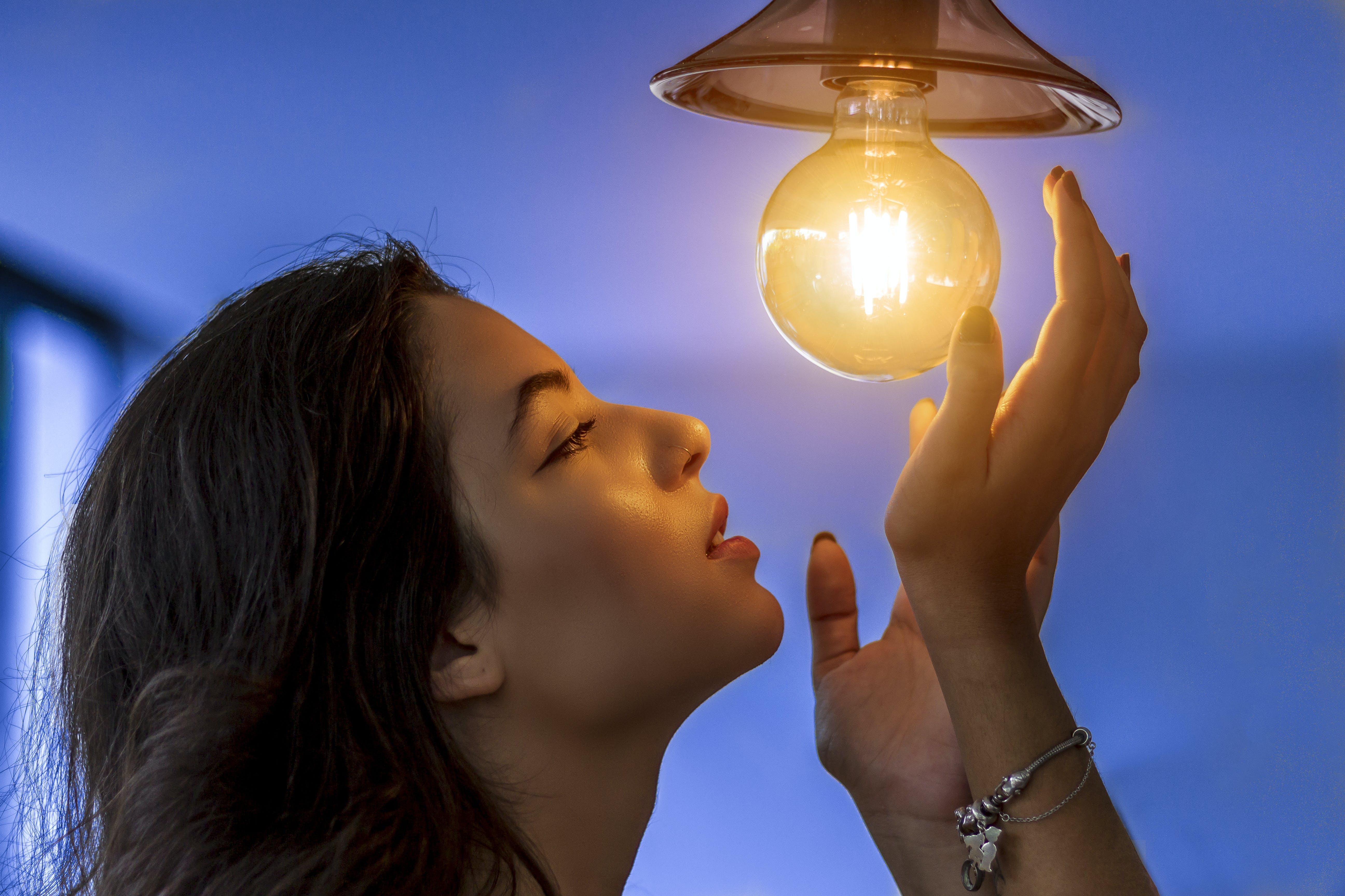 Woman Near Turned-on Light Bulb