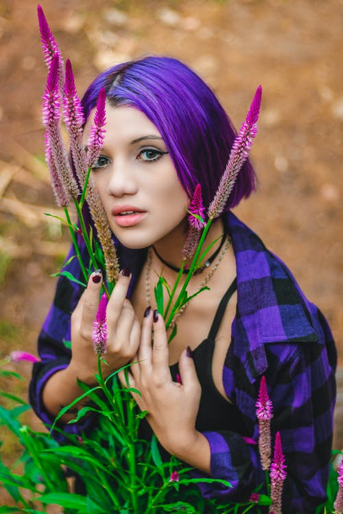 Photo of Purple Haired Woman in Purple and Black Plaid Collared Shirt Next to Purple Flowers