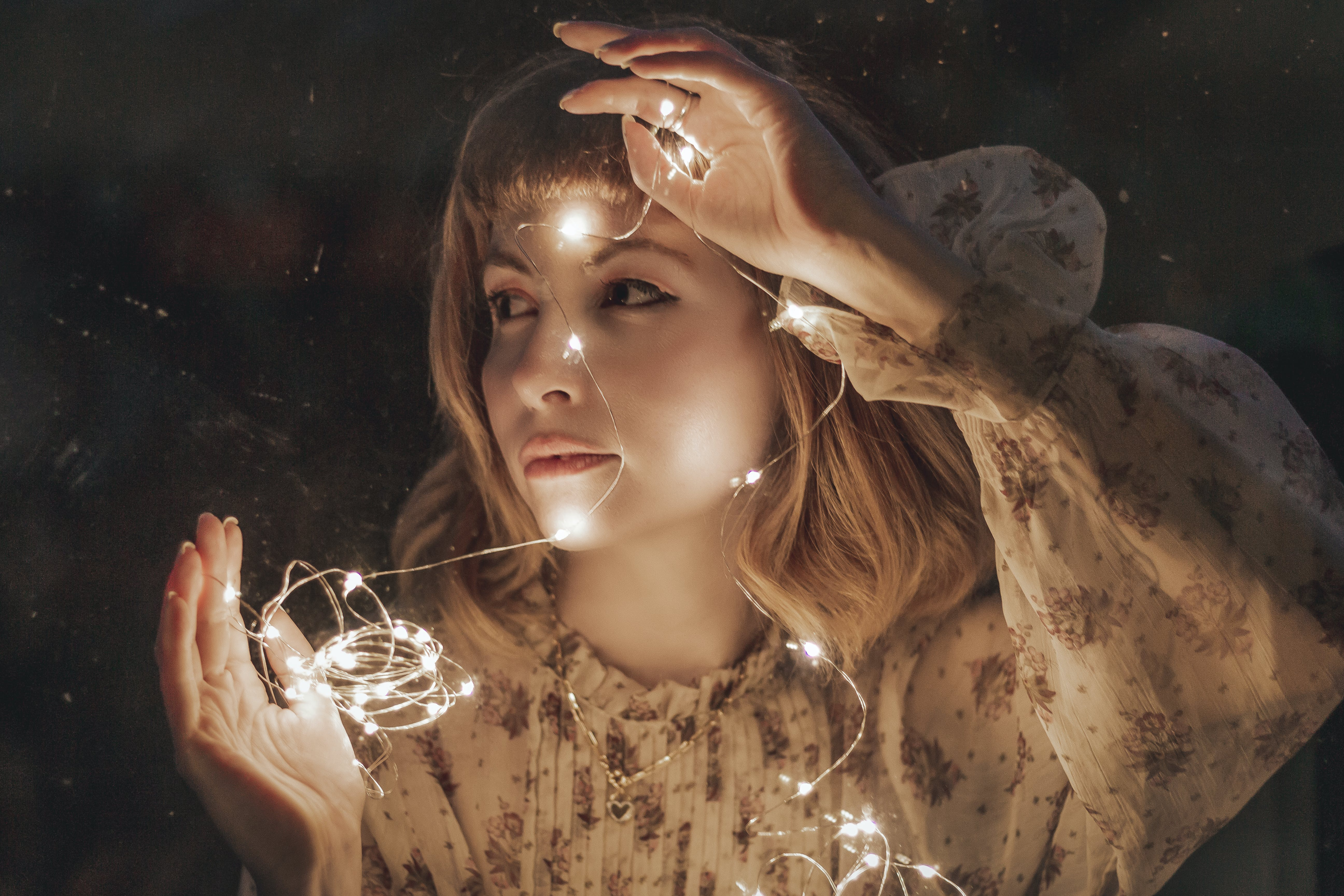 Photo of Woman in White Floral Dress Holding Turned-on String Lights