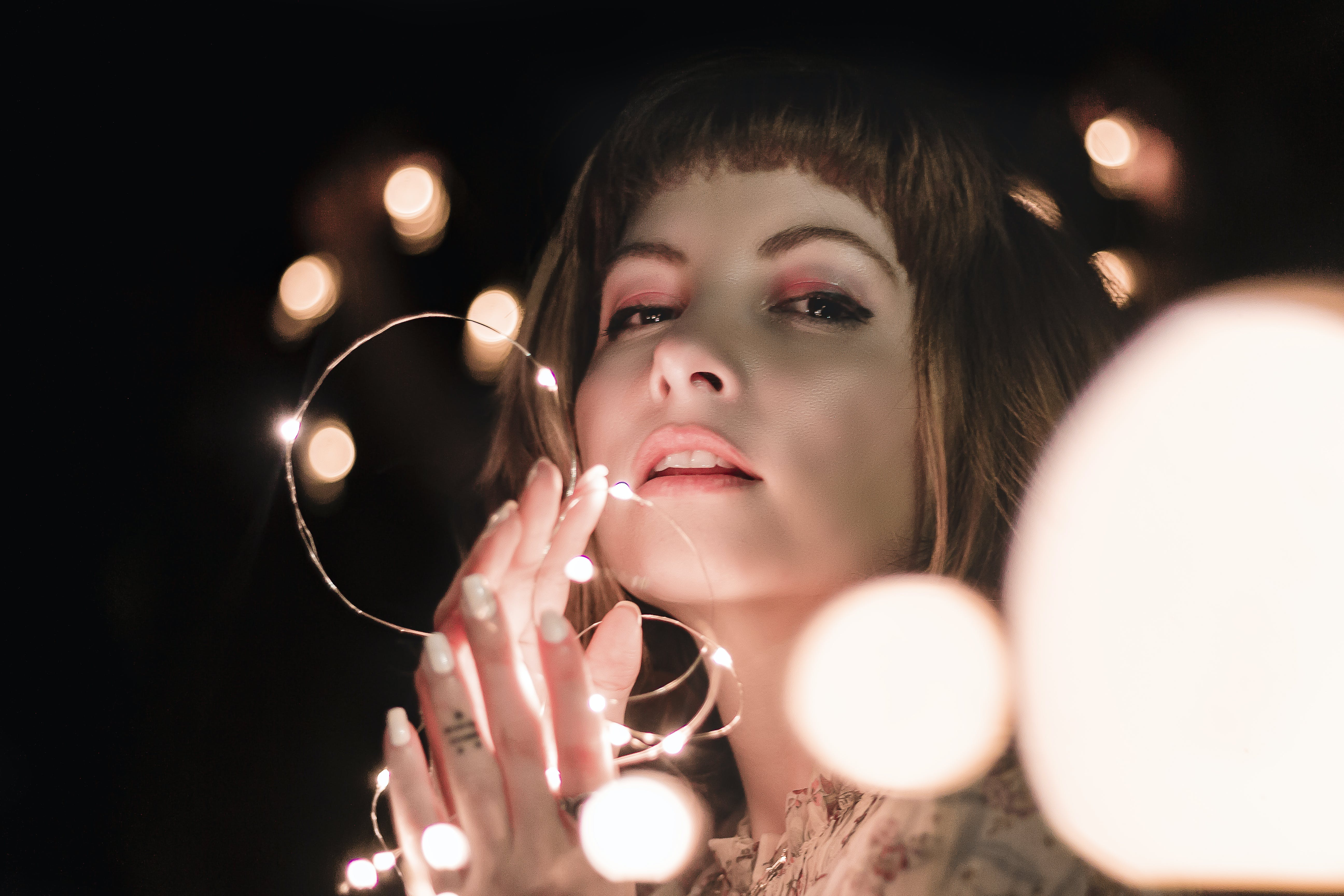Close-up Photo of Woman Posing while Holding Lit String Lights
