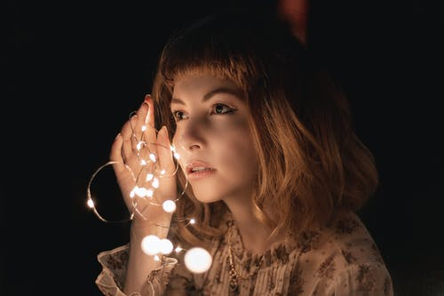 Photo of Woman Holding Lit String Lights