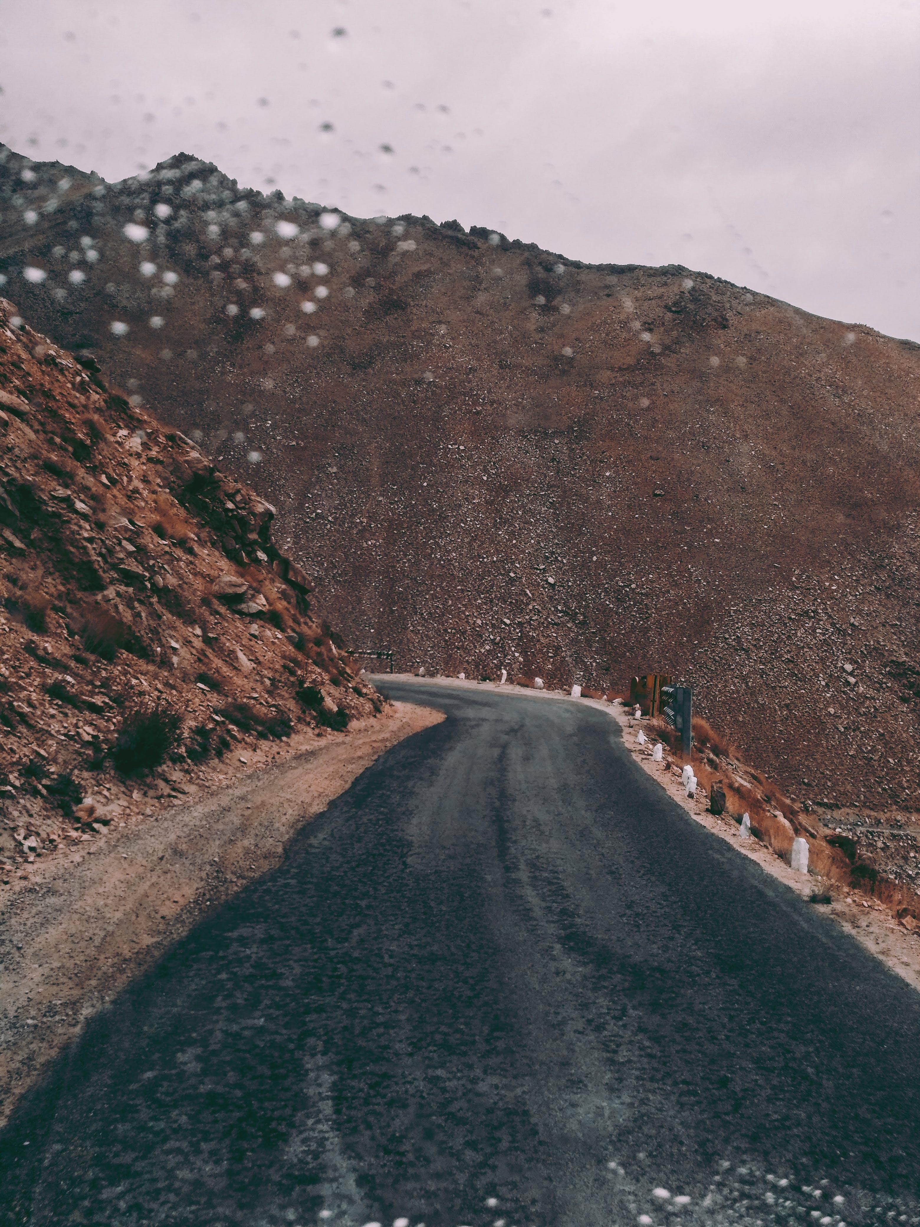 Black Asphalt Road Beside Brown Rock Formation
