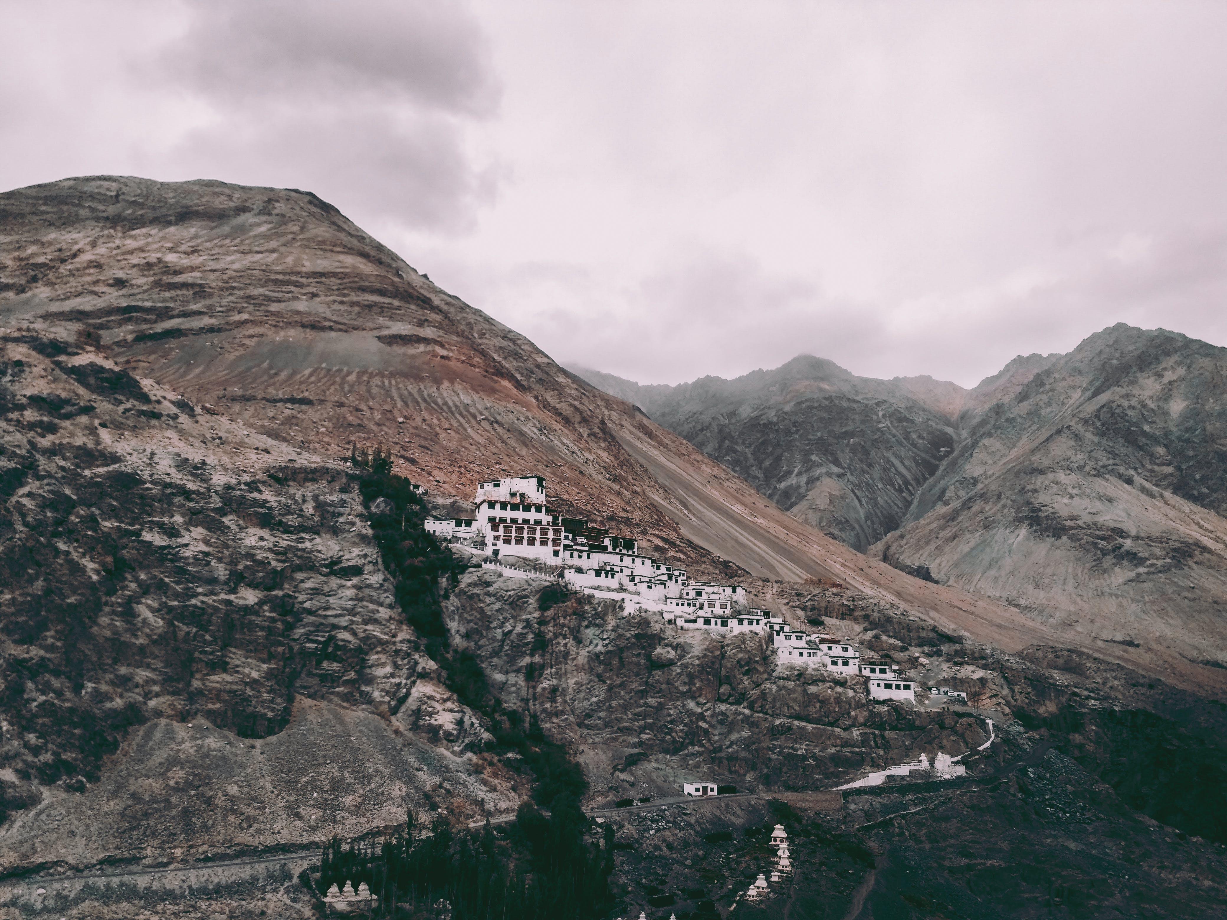 White Concrete Buildings on Rock Mountain Under Gray Sky