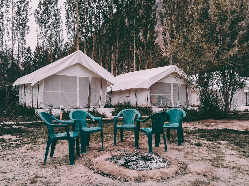 Five Green Plastic Armchairs Near Canopy Tents