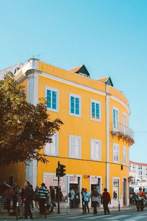 People Walking Beside Yellow Building