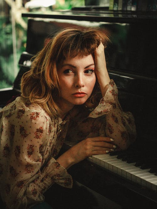 Photo of Woman Leaning On Piano
