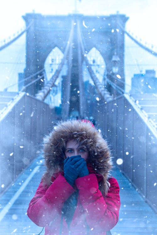 Woman Wearing Red Parka Jacket While Standing on Brooklyn Bridge