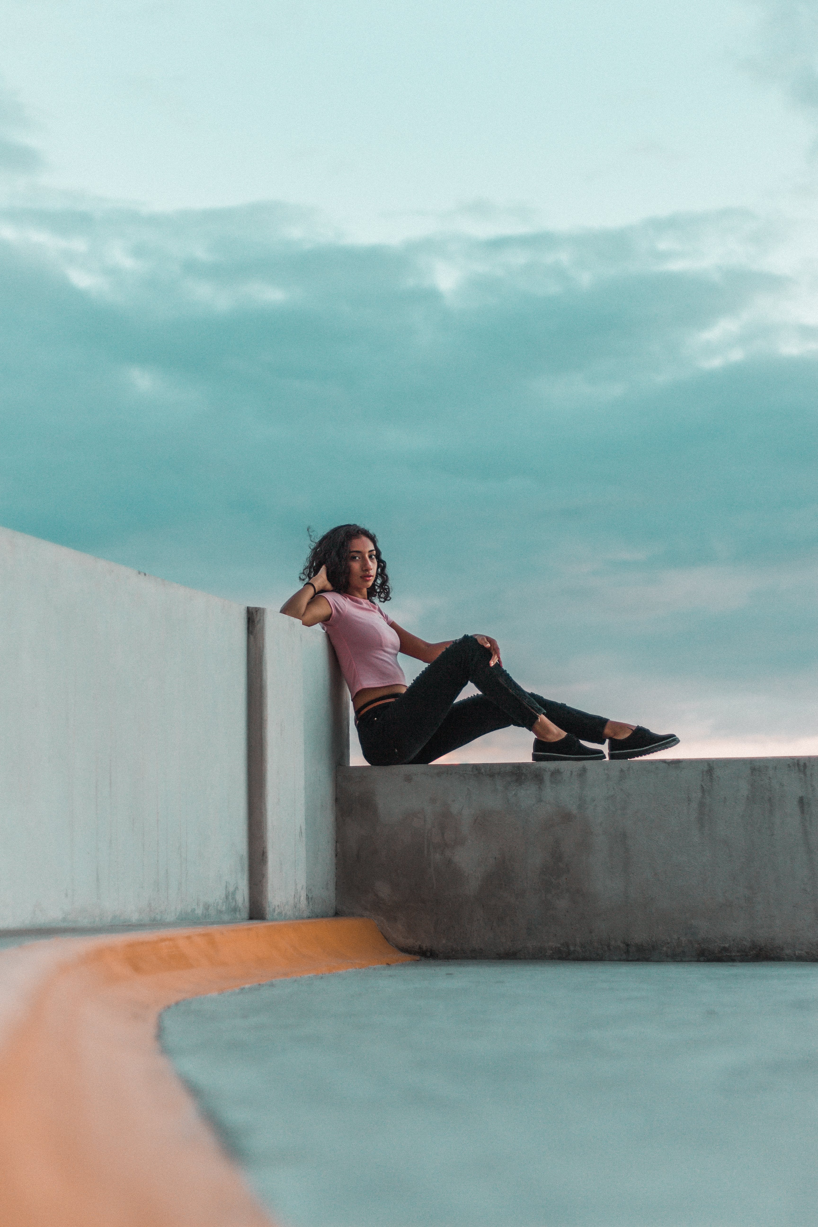 Woman Wearing T-shirt and Pants Leaning on Ledge