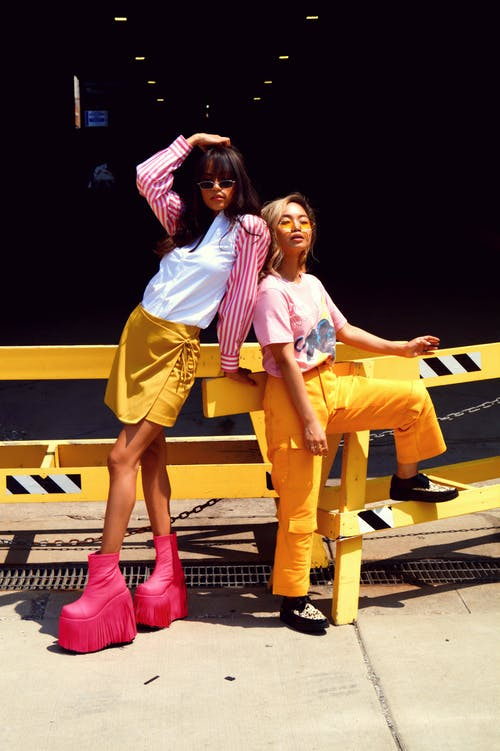 Woman in Pink T-shirt and Yellow Pants Next to Woman in White Shirt With Pink and White Stripe Blazer