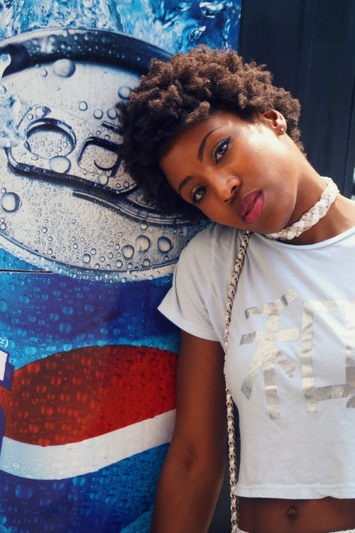 Woman Wearing Crop Top Near Pepsi Poster