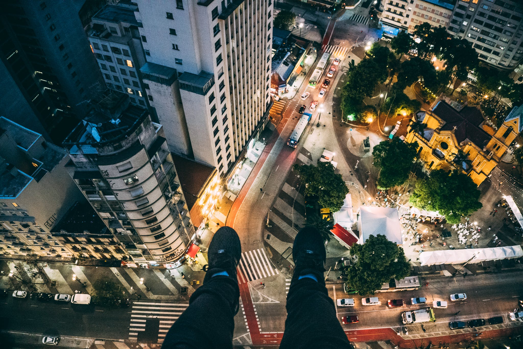 Man Sitting on High Rise Building Taking Photo Below