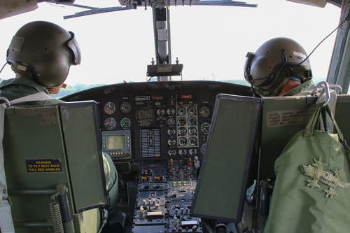 Unrecognizable combat pilots in helicopter cockpit