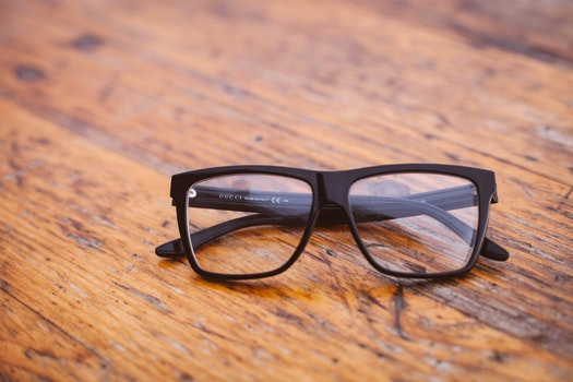 Black Frame Wayfarer Eyeglasses on Brown Wooden Surface