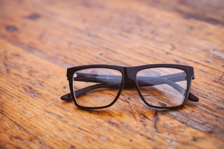 Black Frame Wayfarer Eyeglasses on Brown Wooden Surface