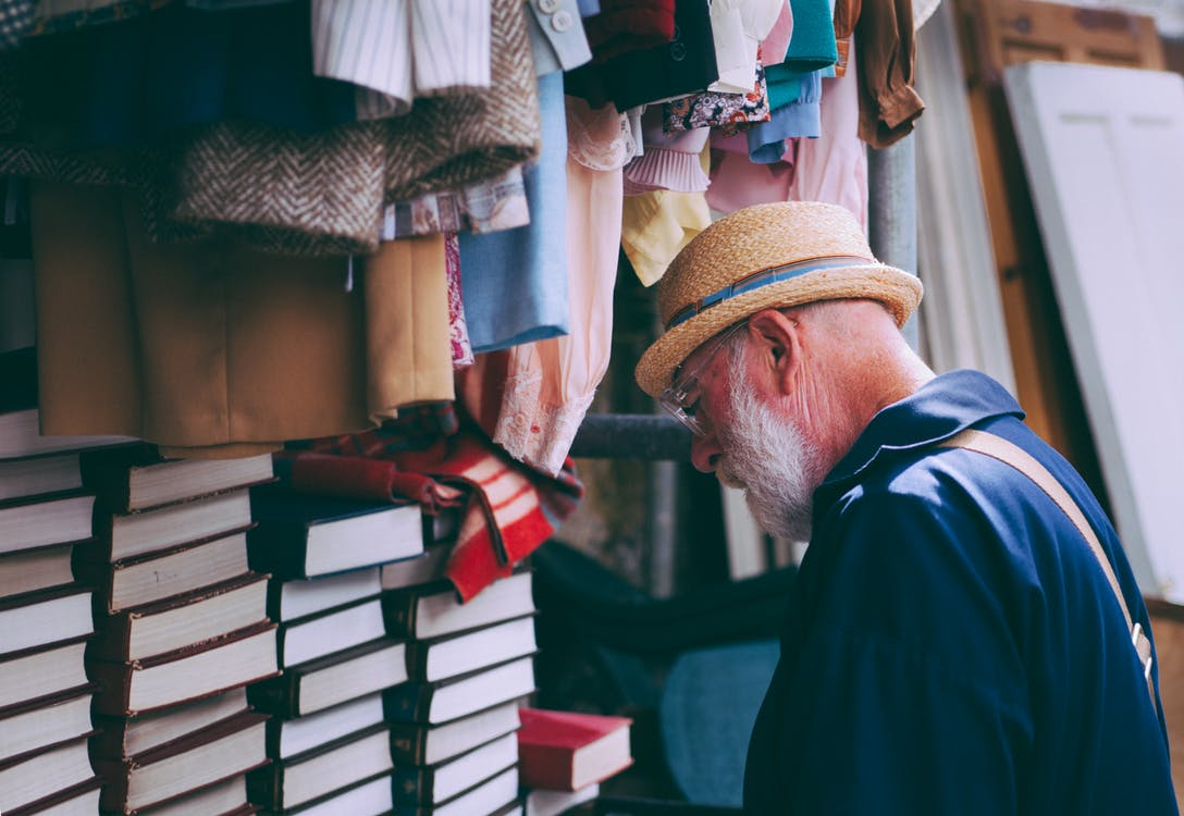 Man in Brown Sun Hat Facing Black Covered Piled Books