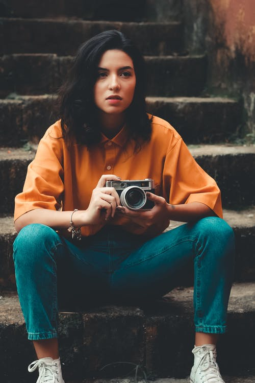 Woman Sitting on Stairs Holding Camera