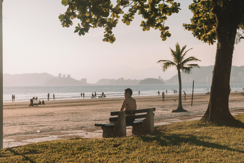 Shirtless Man Sitting on Bench Fronting Beach