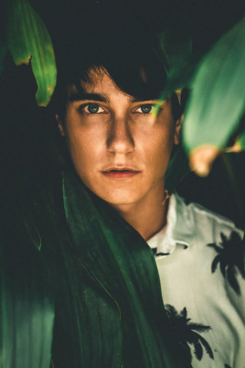 Man in White Collared Shirt Surround by Leaves on Focus Photography