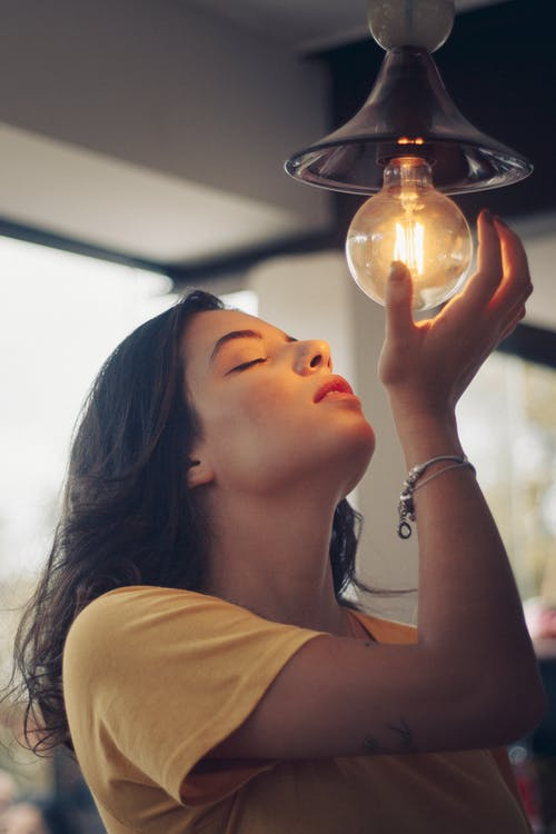 Woman Under Turned-on Pendant Lamp