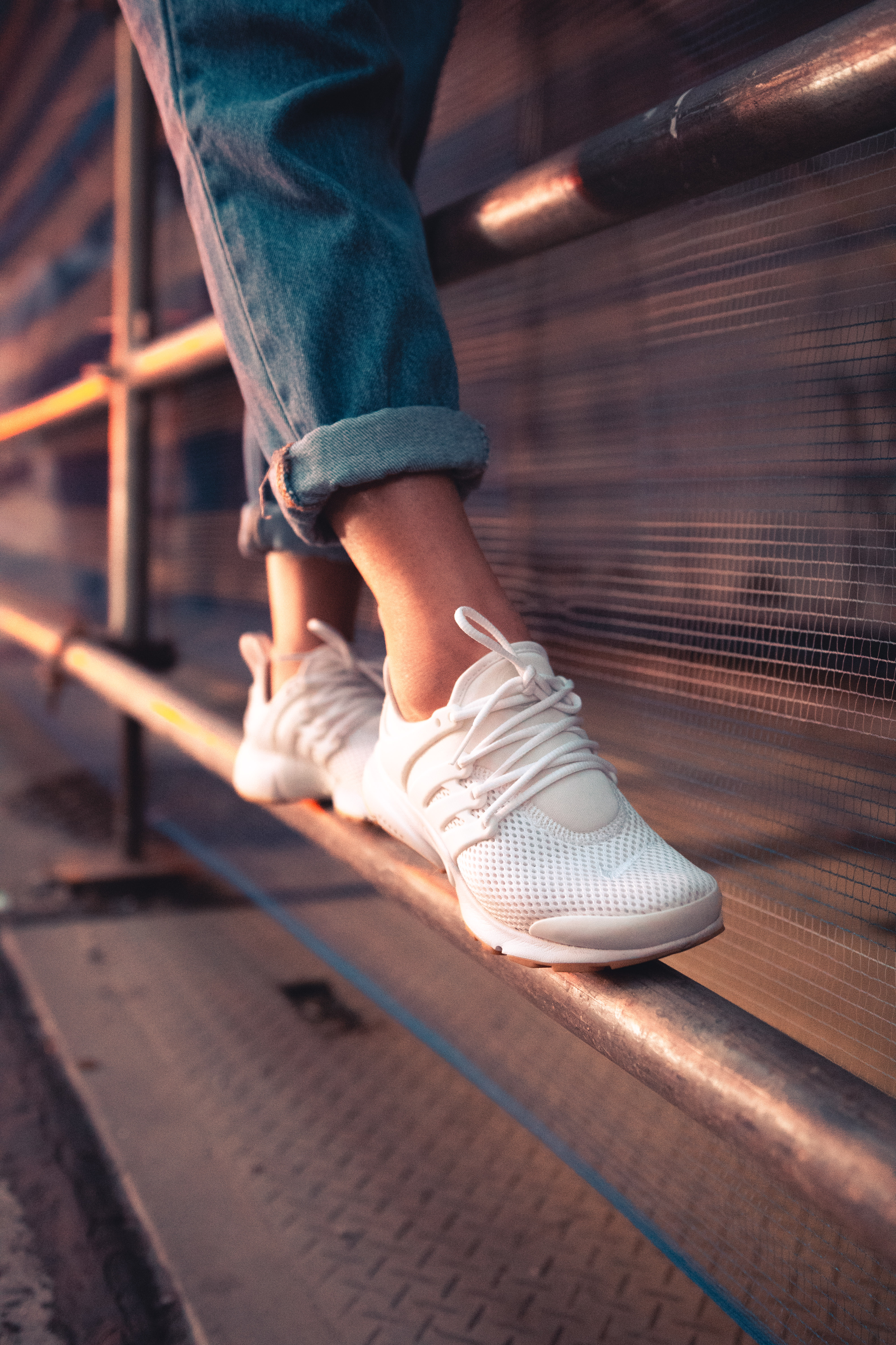 person in blue jeans and white sneakers standing on metal railings