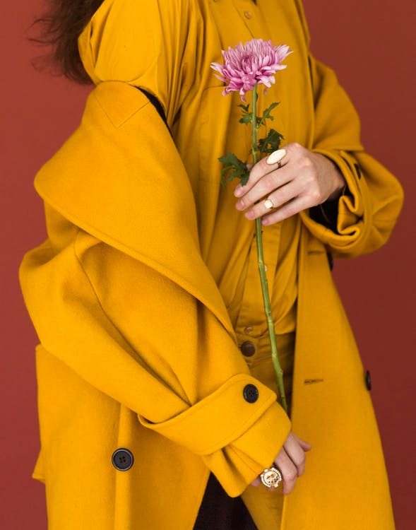 Woman Wearing Yellow Trench Coat While Holding Purple Flower