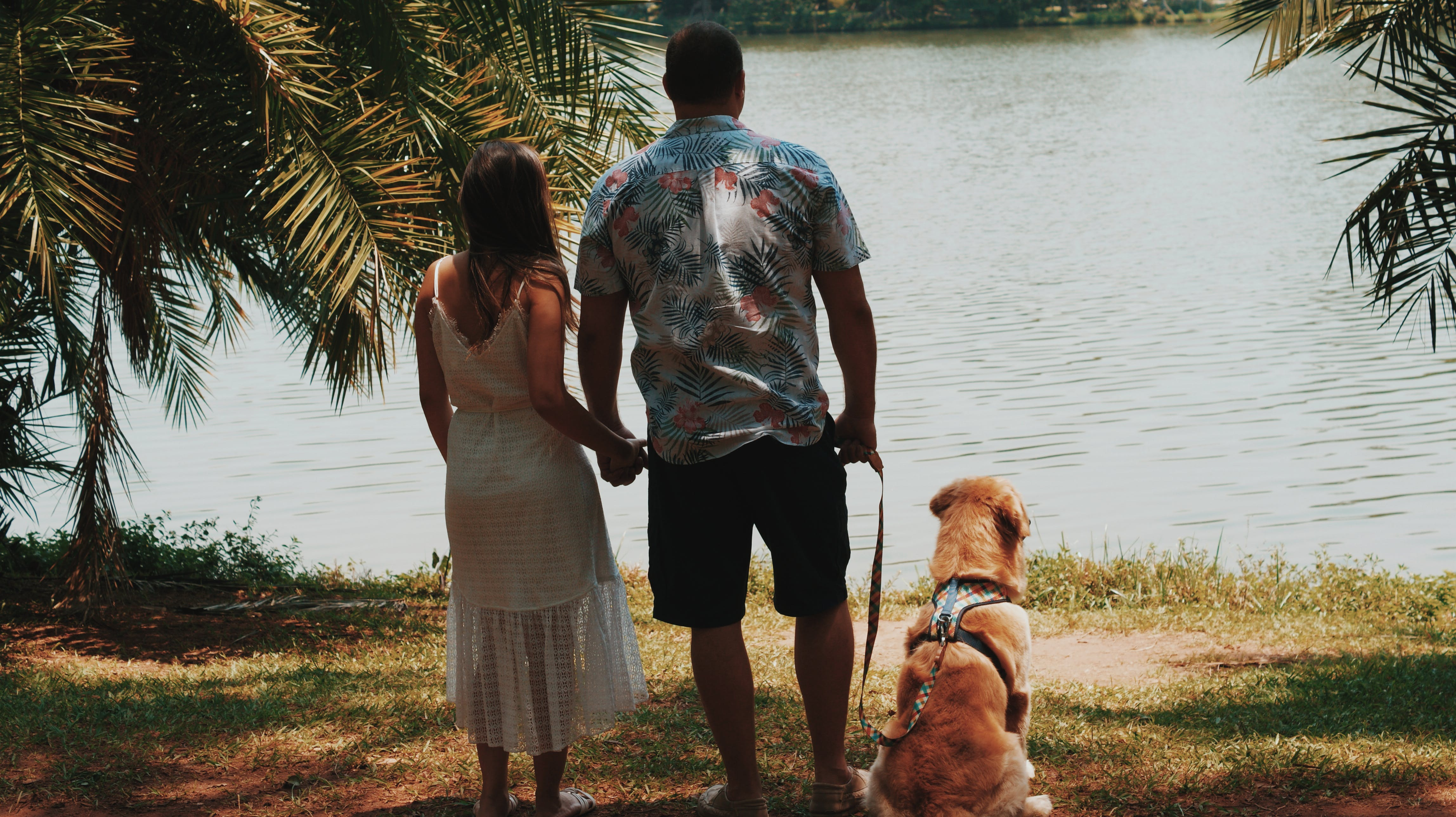 Couple And Dog Standing On Shore