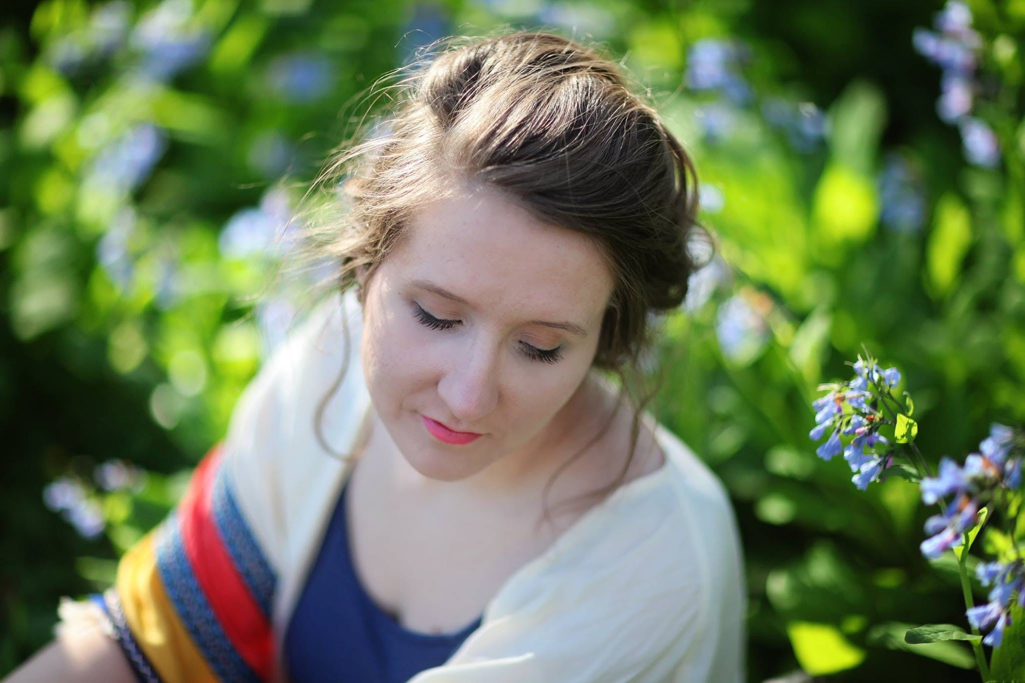 Selective Focus Photography of Woman Beside Blue Petaled Flowers