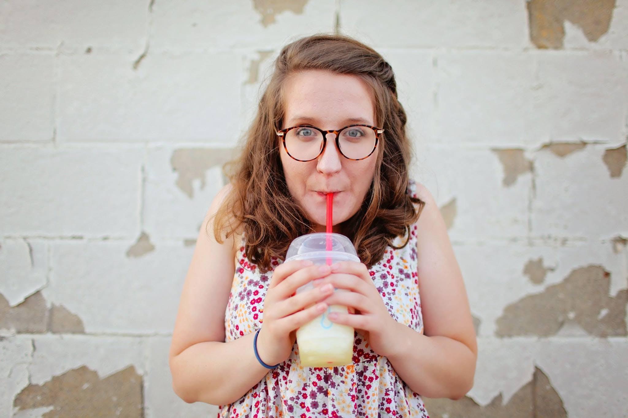 Woman in Black Framed Eyeglasses Drinking