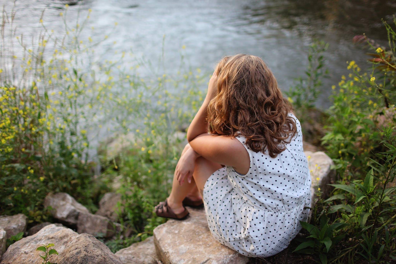 Frau sitzt am Flussufer und hat den Kopf auf die Arme gestützt