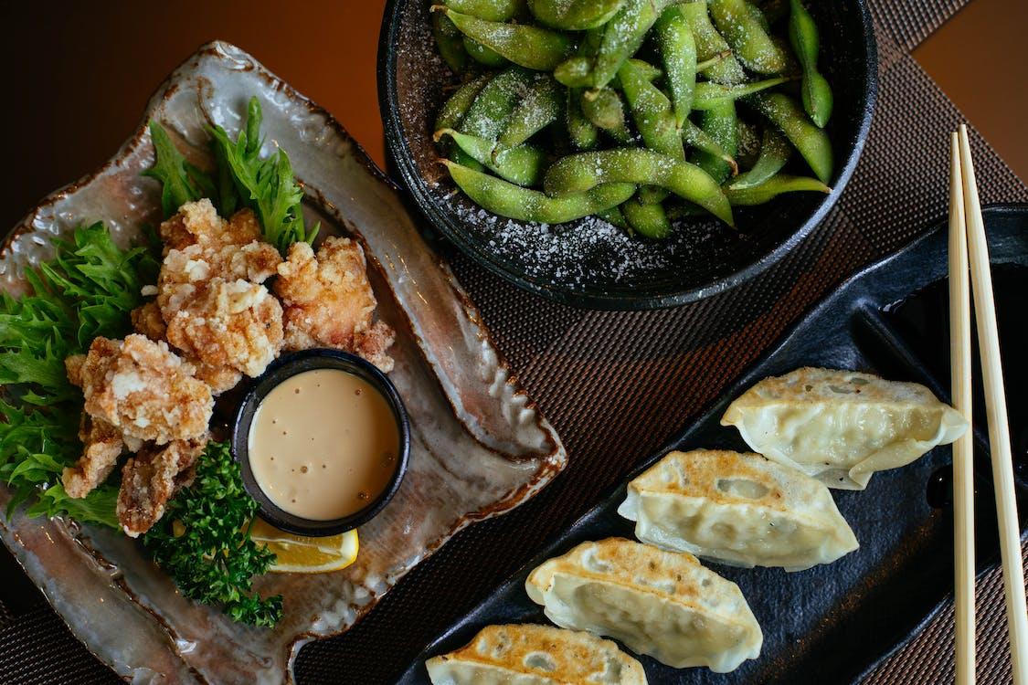 Dumplings on Black Plate Beside Green Beans and Fried Food