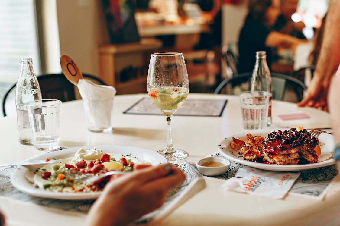 Wine in Clear Glass Near Food on Plate on Table