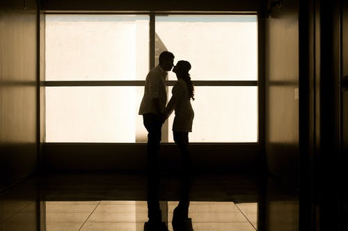 Man and Woman Holding Hands Near Glass Window