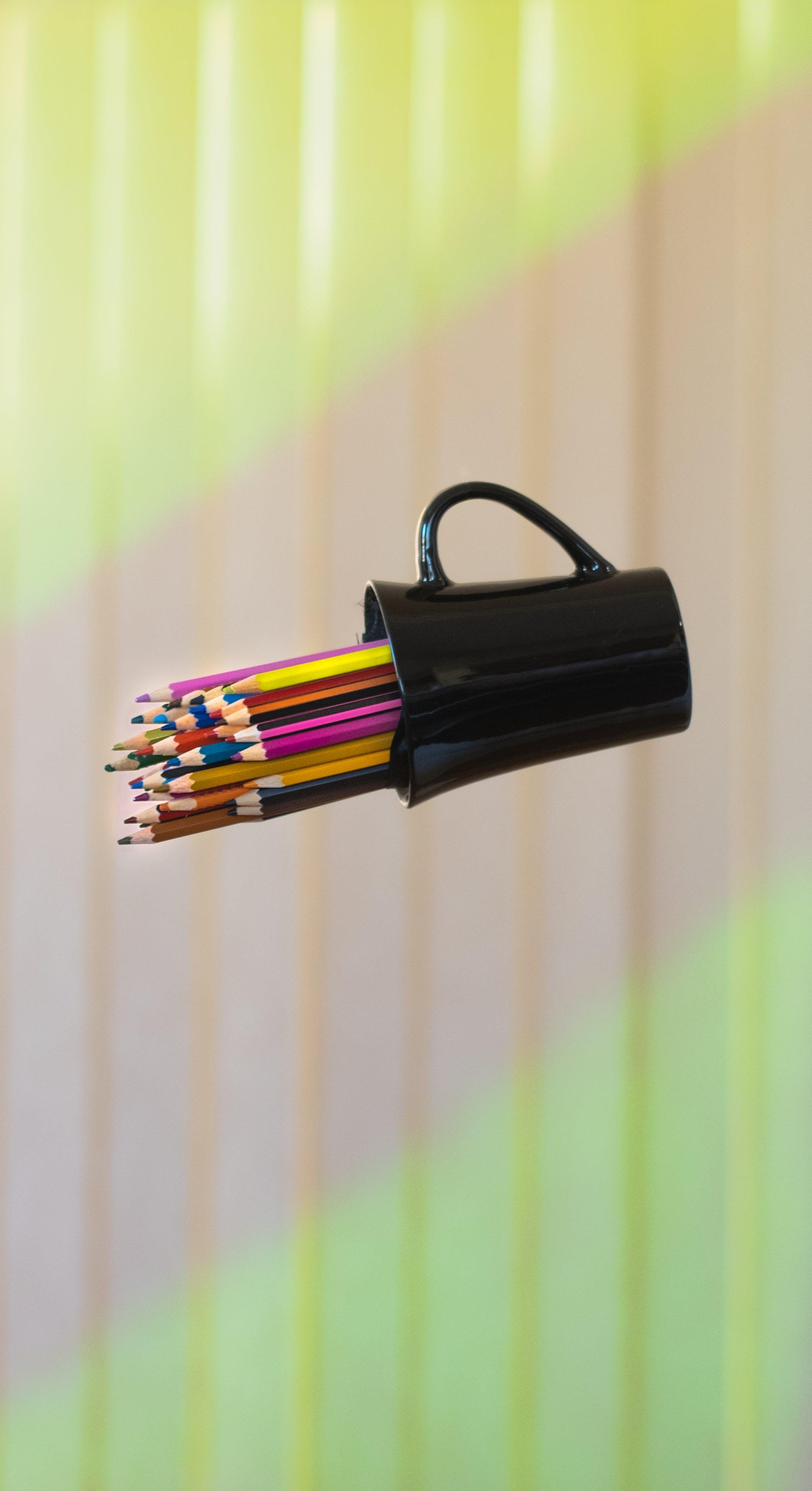 Free stock photo of artistic, black mug, coffee mug, coloured pencils