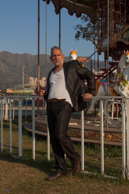 Kostenloses Stock Foto zu dressman, graue haare, karussell, latino