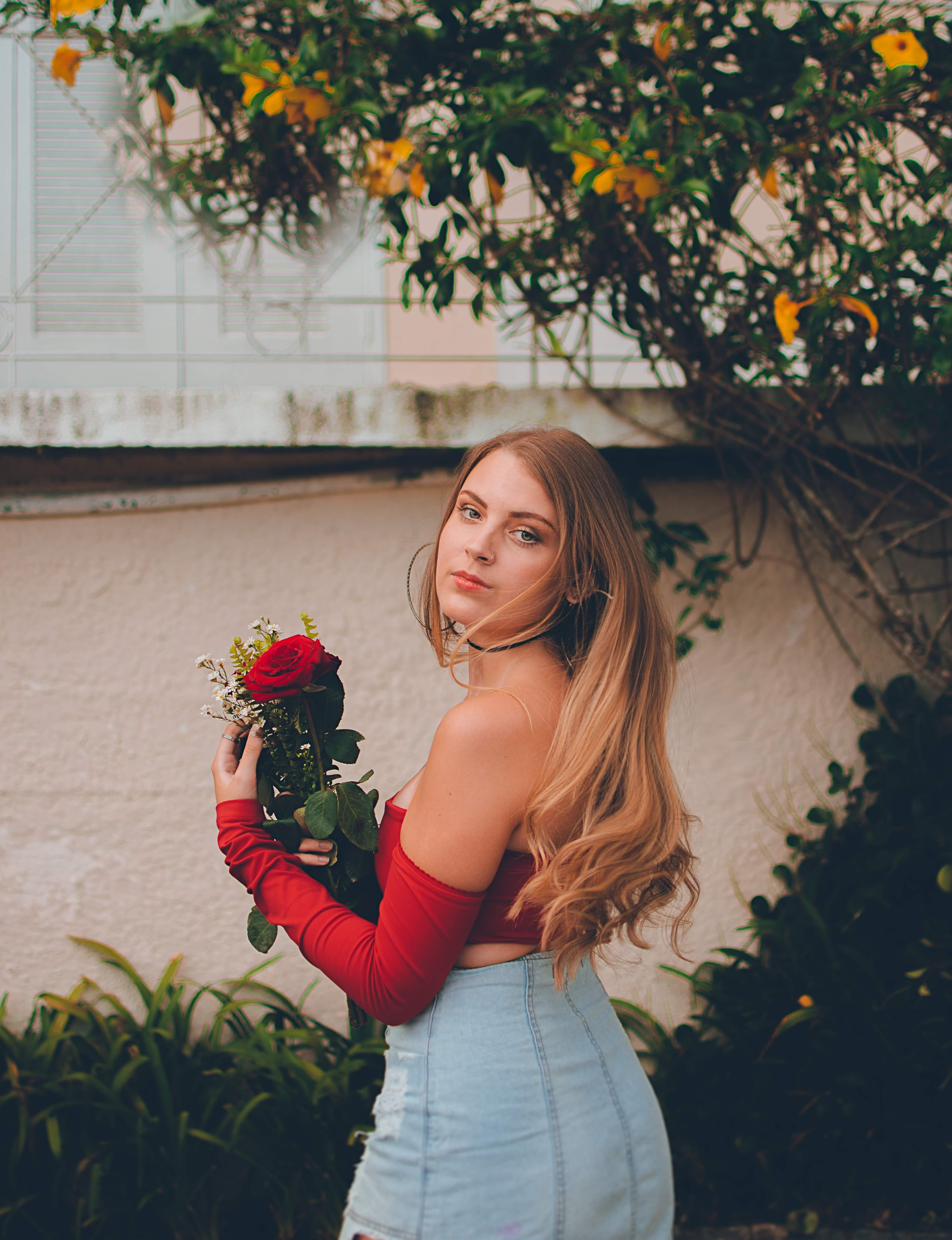 Woman in Red Off-shoulder Top Holding Flower