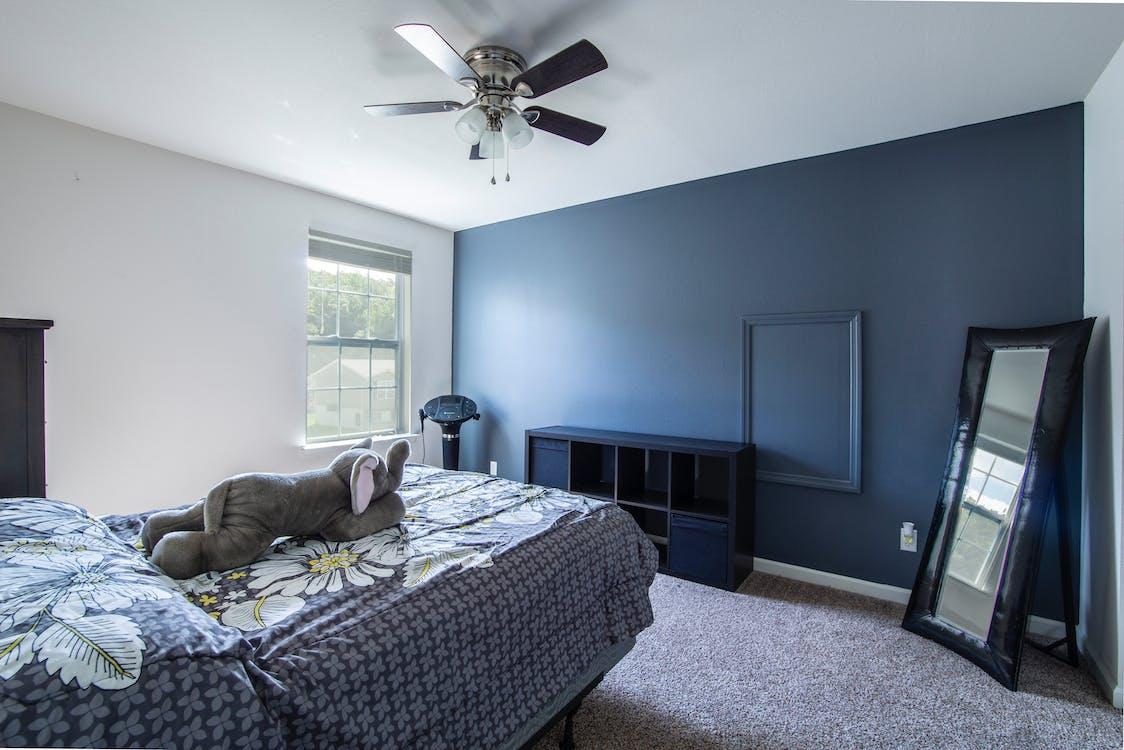 Gray Elephant Plush Toy on Bedspread Near Blue Surface