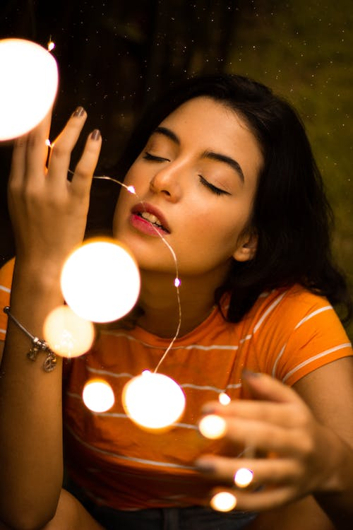 Woman in Orange T-shirt With Her Eyes Closed Holding Lit String Lights