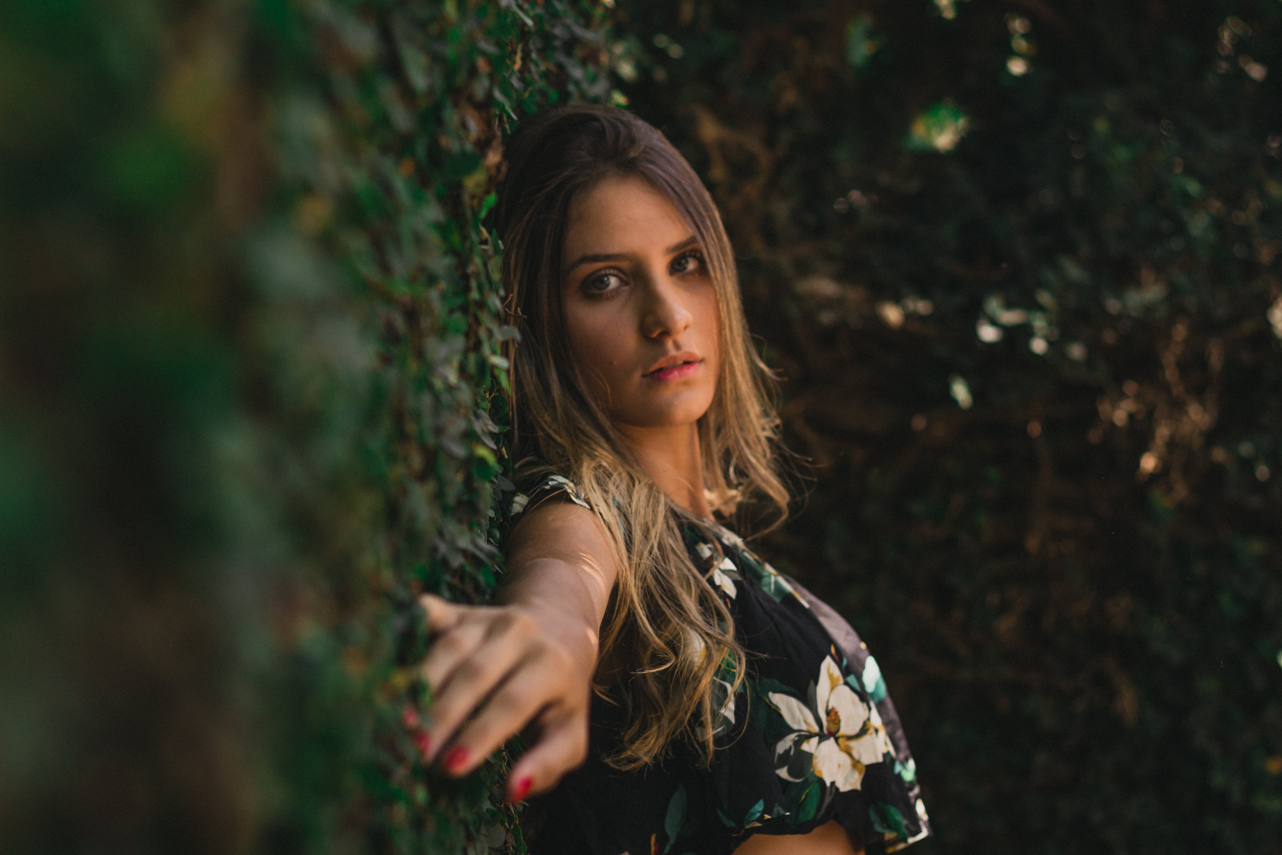 Photo of Woman Leaning on Grass Hedge Wall