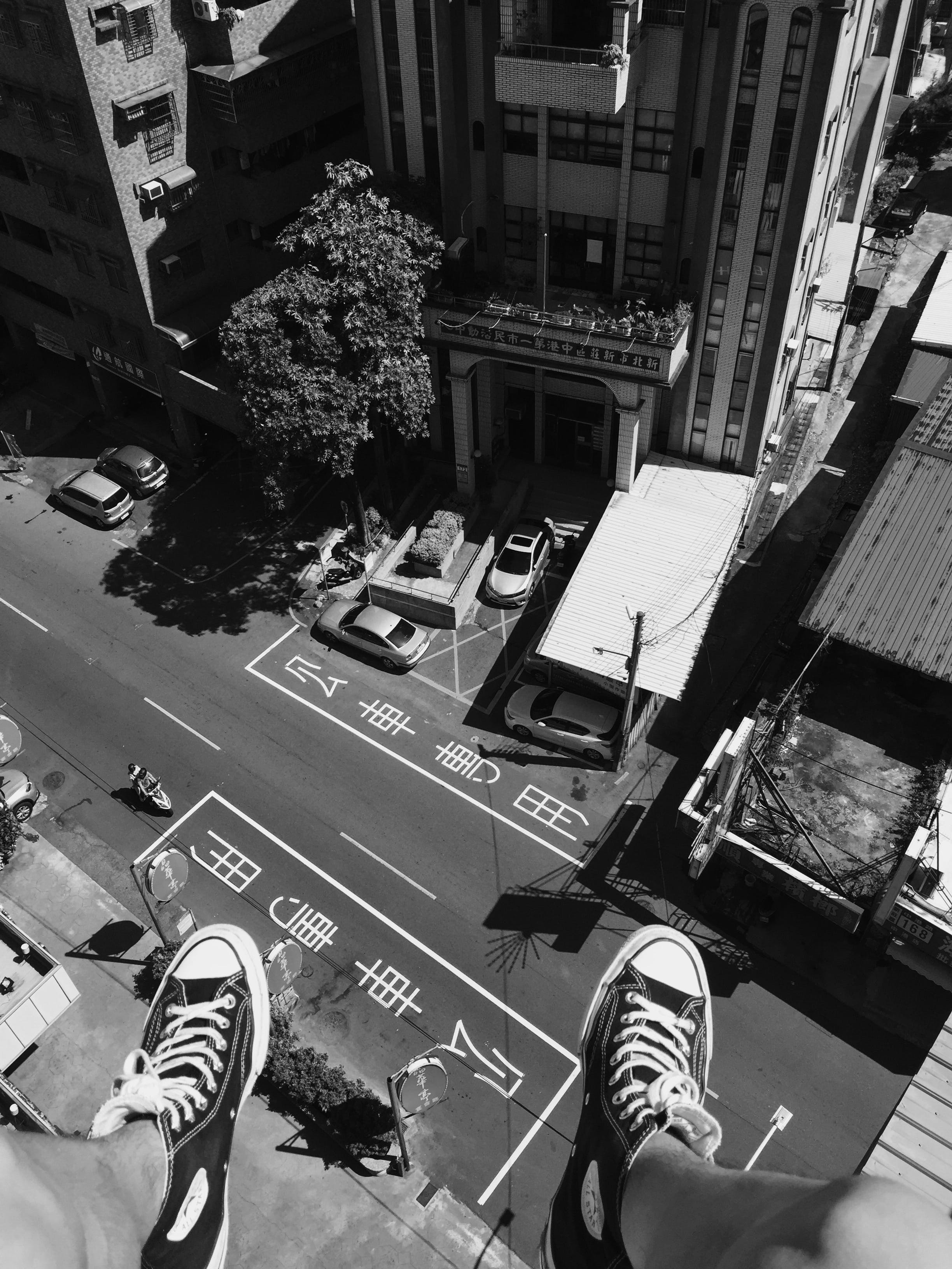 Grayscale Photography Man Wearing All Star Converse High Tops Below in Street and Building