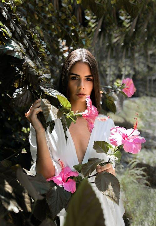 Woman Standing Near Pink-Petaled Flowers