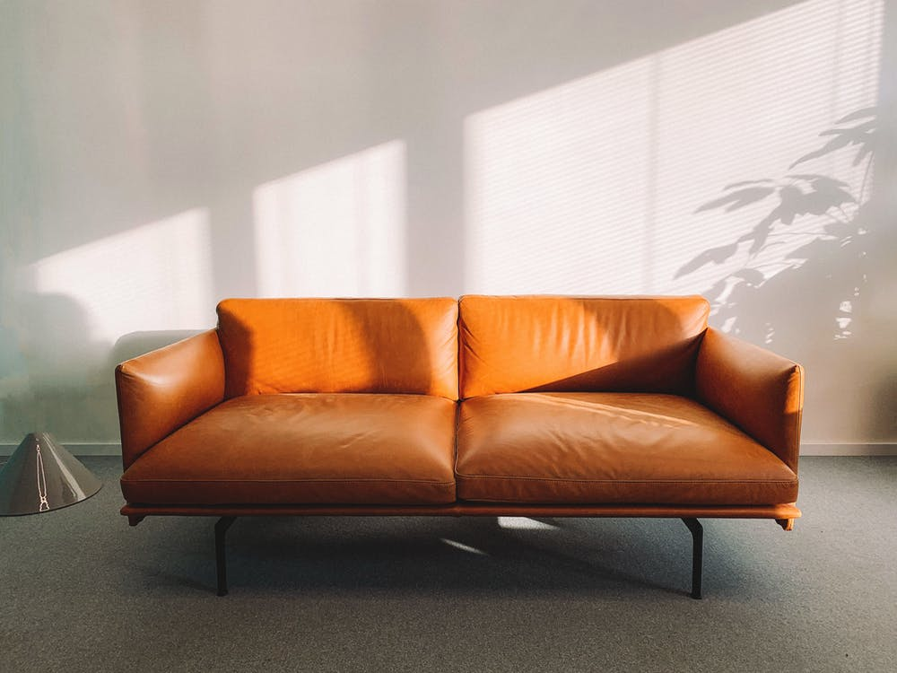 2-seat Orange Leather Sofa Beside Wall